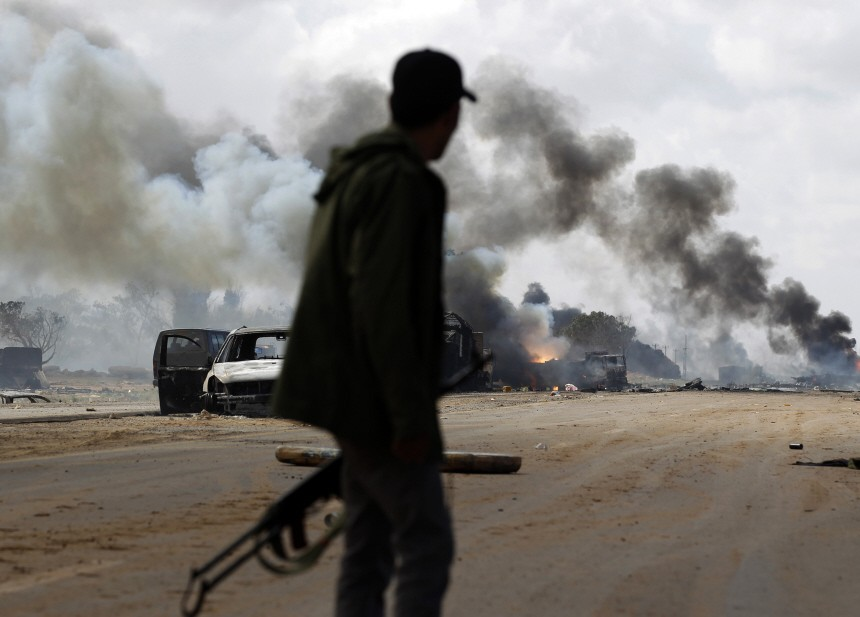 A rebel fighter looks at a burning vehicle belonging to forces loyal to Libyan leader Muammar Gaddafi after an air strike by coalition forces, between Benghazi and Ajdabiyah