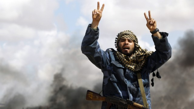 A rebel fighter shouts in front of a burning vehicle belonging to forces loyal to Libyan leader Muammar Gaddafi after an air strike by coalition forces, between Benghazi and Ajdabiyah