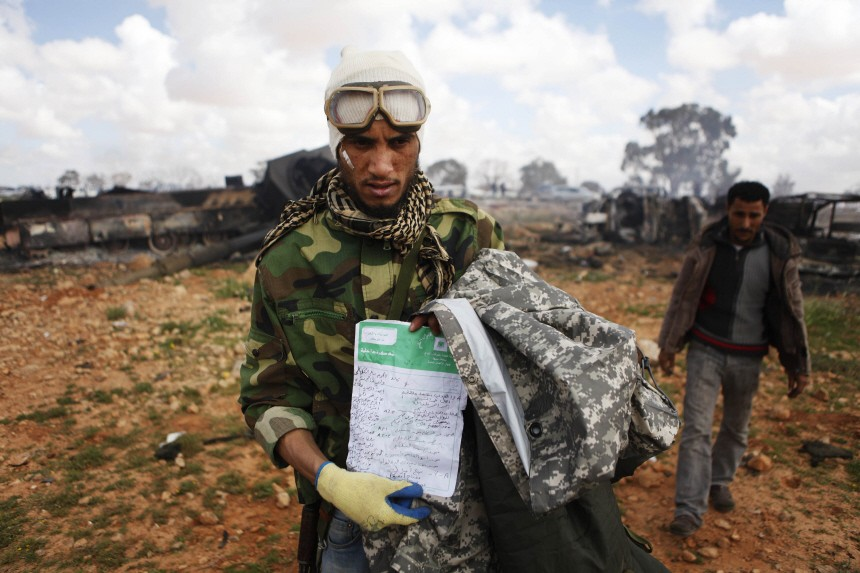 A rebel fighter shows a Libyan government document near Benghazi