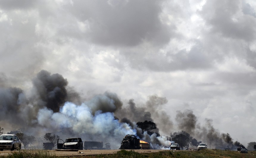 Vehicles belonging to forces loyal to Libyan leader Muammar Gaddafi burn after an air strike by coalition forces, along a road between Benghazi and Ajdabiyah
