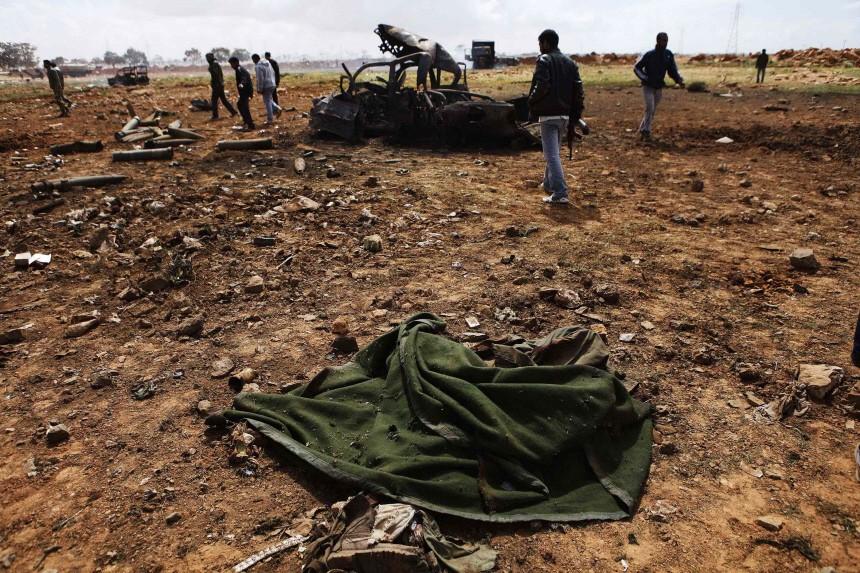 The body of a Muammar Gaddafi loyalist soldier lies near Benghazi