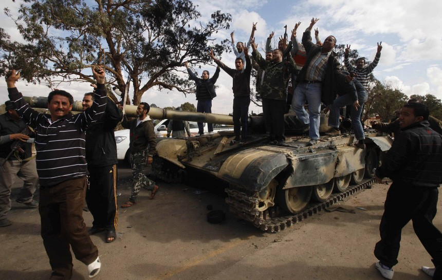 People celebrate atop a destroyed tank belonging to forces loyal to Libyan leader Muammar Gaddafi after an air strike by coalition forces, along a road between Benghazi and Ajdabiyah