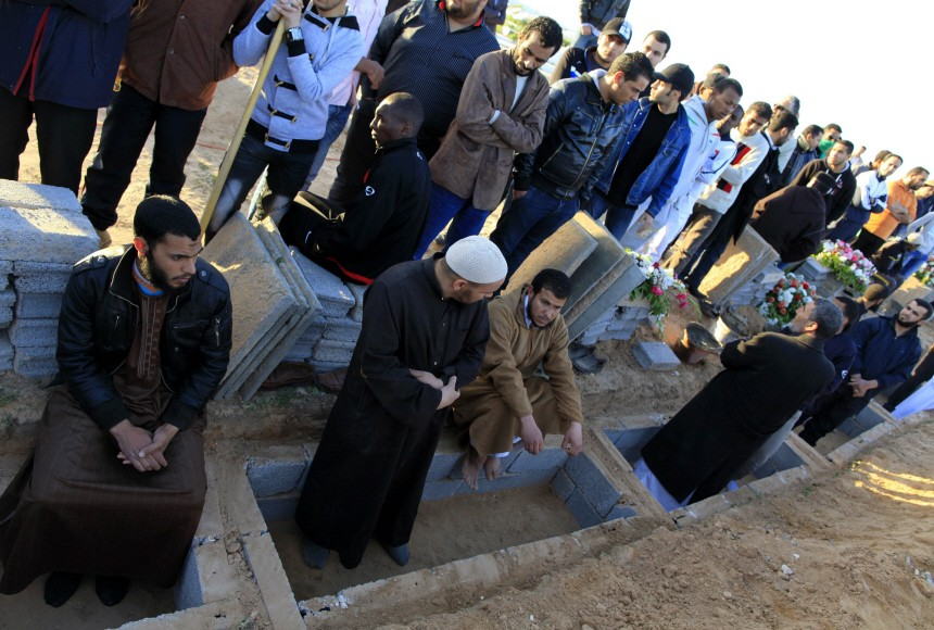 Libyans mourn during the funeral of the people who were killed after air strikes by coalition forces, at the martyrs' cemetery in Tripoli