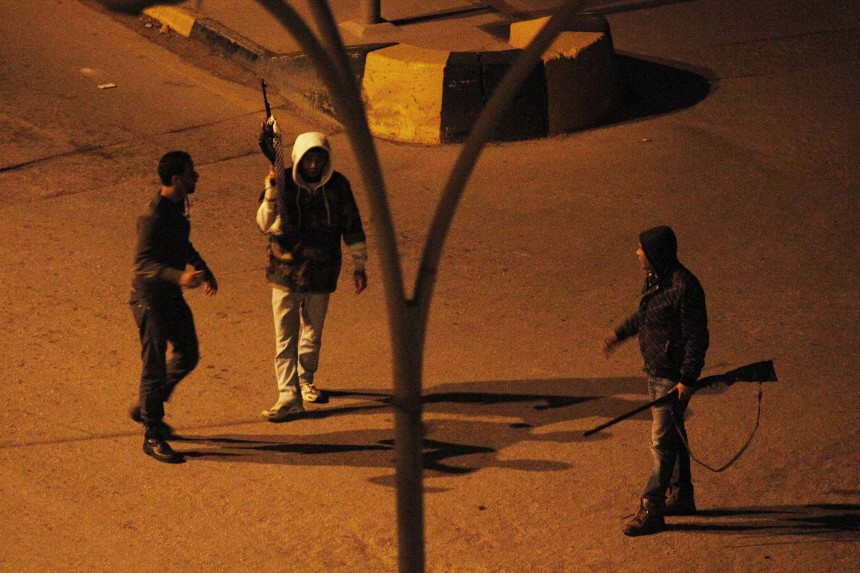 A rebel fighter set up a check point during a night time gun battle in downtown Benghazi