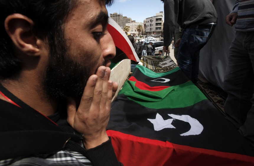 A mourner reacts next to coffins containing bodies of Libyans killed by forces loyal to Libyan leader Muammar Gaddafi, during a funeral in Benghazi