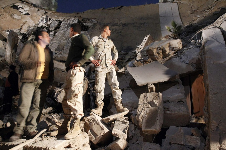Libyan army soldiers stand on a building, destroyed in what the government said was a western missile attack, inside Bab Al-Aziziyah