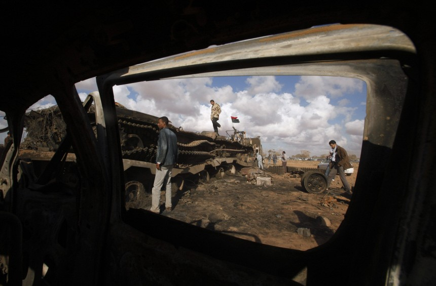 People stand amidst wreckage of tanks after a coalition air strike, along a road between Benghazi and Ajdabiyah