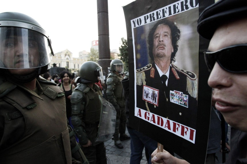 A demonstrator holds a poster with the picture of Libya's leader Muammar Gaddafi is front of riot policemen during a protest against the visit by U.S. President Barack Obama, in Santiago