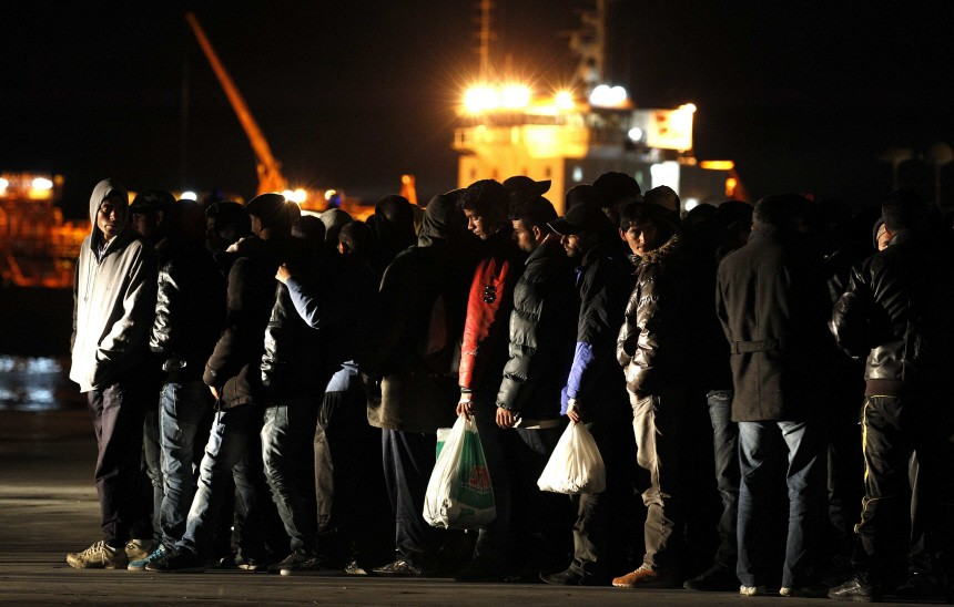 People fleeing the unrest in Tunisia stand in line on the wharf after arriving at Lampedusa