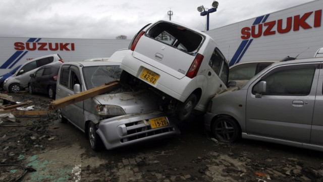 New and used cars are lay scattered in the rubble in front of a S