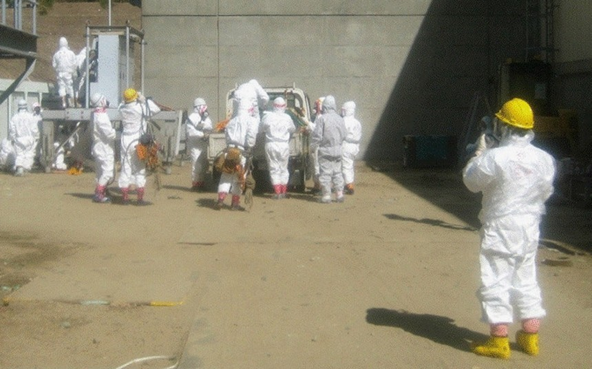 Handout photo from Tokyo Electric Power Co. shows workers outside the Fukushima Daiichi Nuclear Power Plant in Tomioka