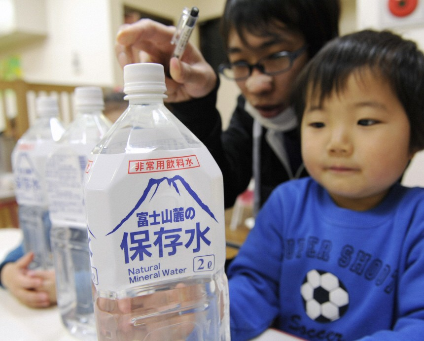 A child holds a bottle of emergency long shelf-life mineral water distributed at a nursery school in Tokyo