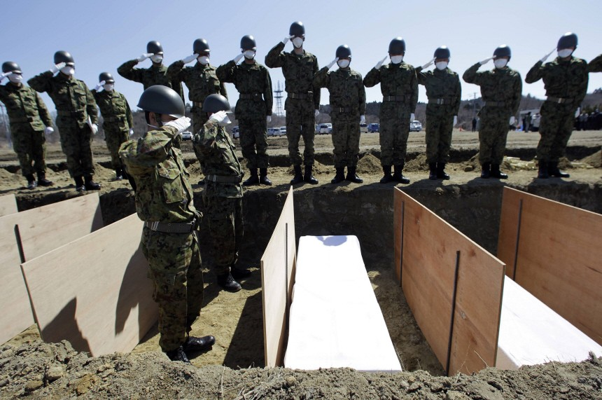 Members of a Japan Ground Self Defense Force unit salute after placing a coffin of a victim from the earthquake and tsunami inside a burial site at a temporary mass grave site in Higashi-Matsushima
