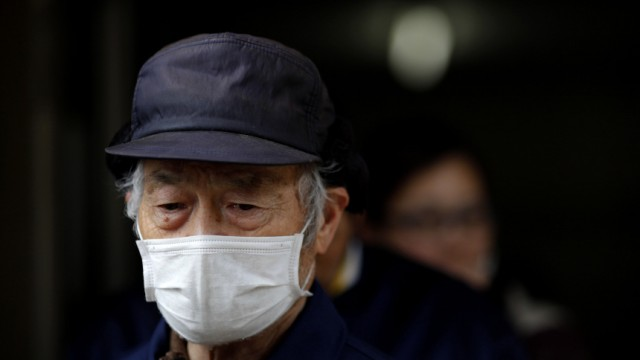A man waits in line during a food distribution at an evacuation center for victims of the earthquake and tsunami in Otsuchi town, Iwate Prefecture in northern Japan