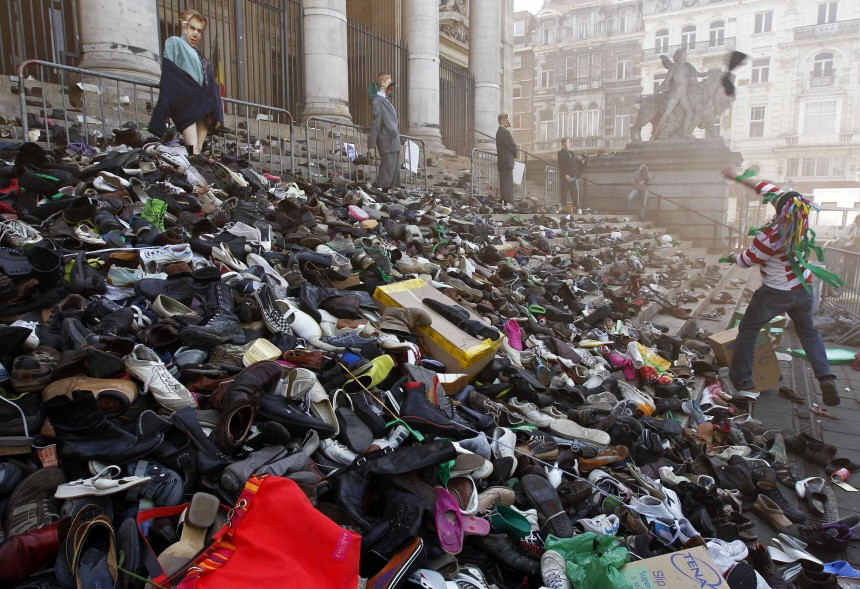 A worker in the non-profit sector throws his shoes onto the steps of the stock exchange building in Brussels