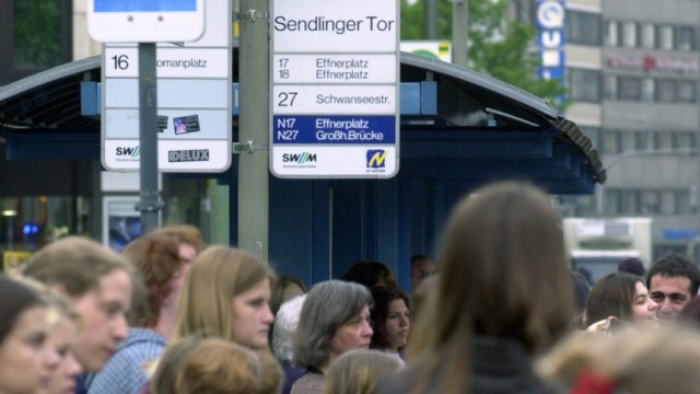 Menschen an Straßenbahnhaltestelle in München