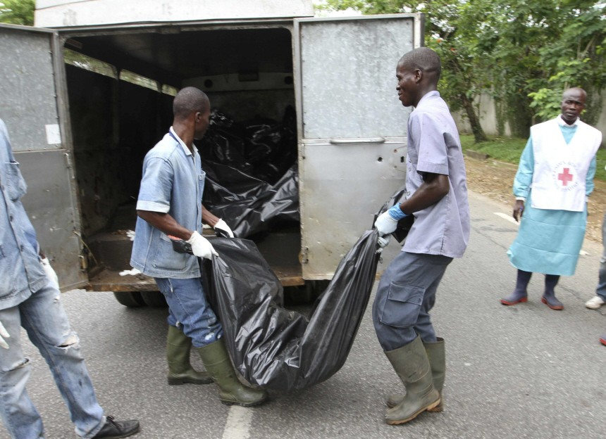 Red cross members remove a body from a street in the Cocody district of Abidjan