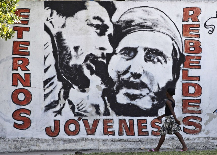 A child walks past a mural depicting former Cuban leader Castro and late revolution leader Guevara in Havana