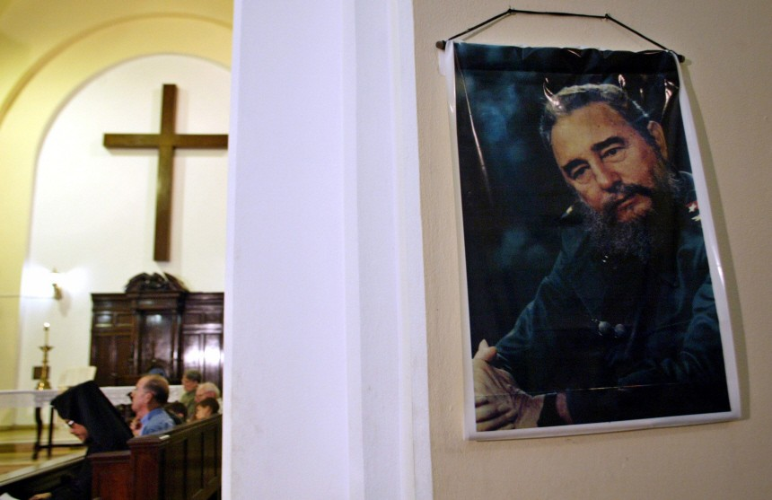 Photograph of Cuba's President Castro hangs on wall as people pray in Havana