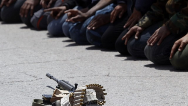 A weapon and bullets are seen as rebel fighters pray near the front line along the western entrance gate of Ajdabiyah