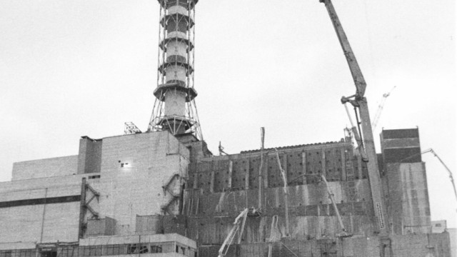 WORKERS AT CHERNOBYL NUCLEAR POWER PLANT HOLD A BANNER