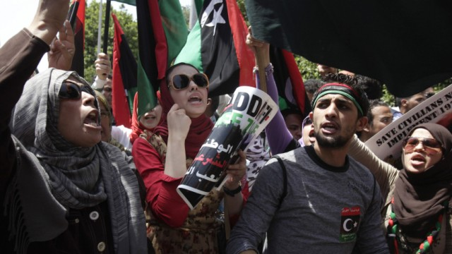 Libyan protesters chant anti-Gaddafi slogans during a protest in front of the Arab League headquarters in Cairo
