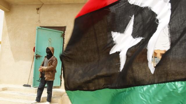 A rebel fighter stands guard behind a Kingdom of Libya flag at Dehiba