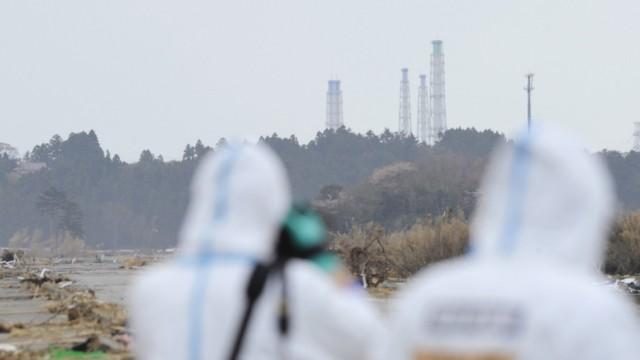 Atomkatastrophe in Japan: Experten in Sicherheitsanzügen vor der Atomanlage Fukushima-Daiichi - die Radioaktivität ist um das 250fache gestiegen.