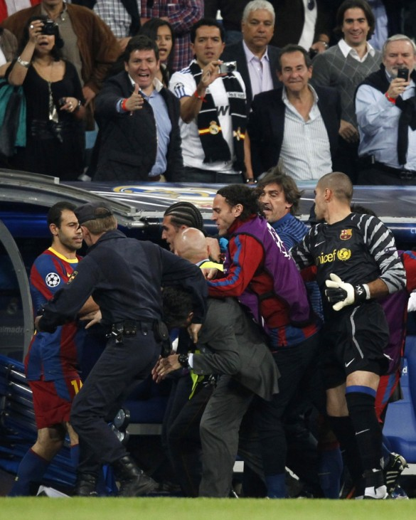 A policeman and a security officer separate Real Madrid's delegate Chendo and Barcelona's goalkeeper Pinto after fighting during their Champions League semi-final first leg soccer match in Madrid