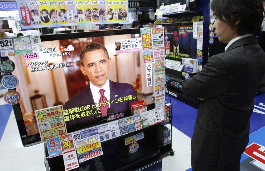 A man watches a television showing the U.S. President Barack Obama addressing, at an electronic shop in Tokyo