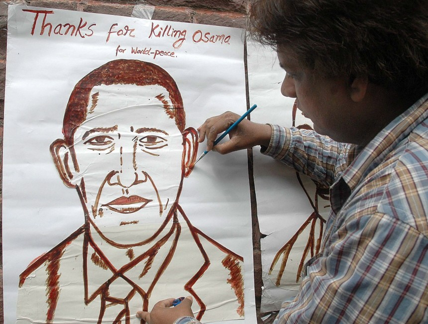 An Indian peace activist paints a portrait of US President Barack