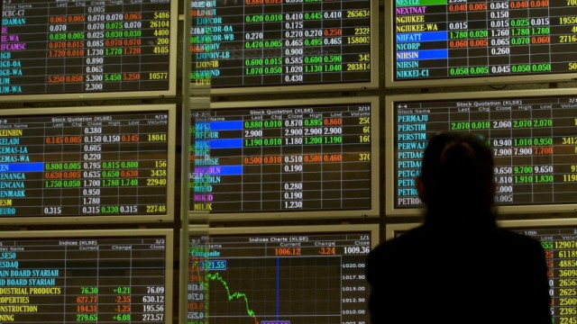An investor monitors stock market prices at a trading gallery in Kuala Lumpur