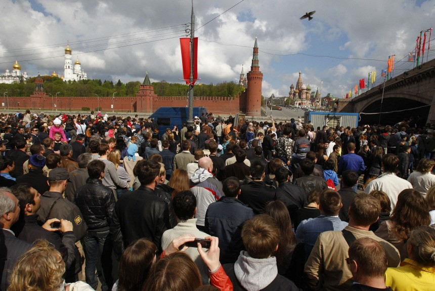 People watch Russian military personnel as they march on the opposite embankment of the Moskva river during a military parade on the Victory Day in Moscow