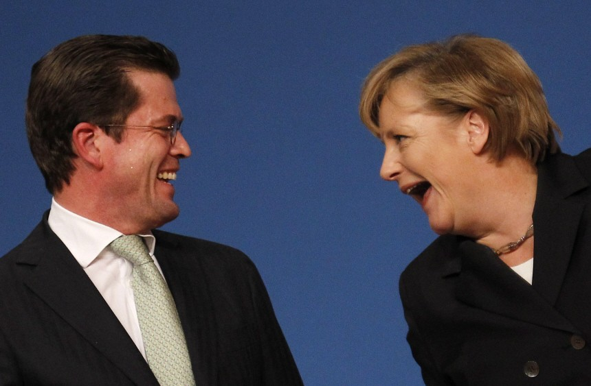 German Defence Minister Karl-Theodor zu Guttenberg of the Bavarian Christian Social Union party CSU acknowledges applause from the congress of sister party, the Christian Democratic Union CDU as he stands next to CDU leader Merkel in Karlsruhe