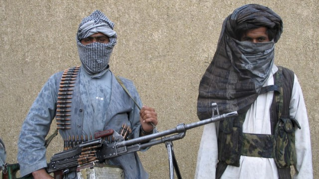 Taliban guerrilla leader  stands next to a Taliban fighter at a secret base in eastern Afghanistan   File photo