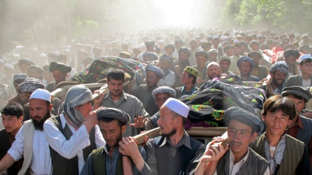Afghans carry the bodies of people killed overnight after a raid by NATO and Afghan forces, during a protest in Taloqan