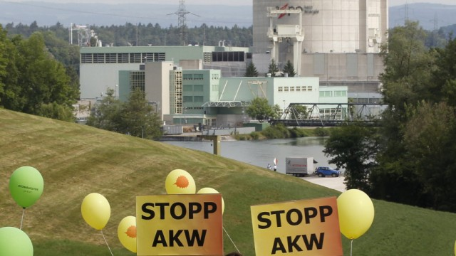 Protestors carry posters demanding a stop to nuclear power plants as they march in front of the power plant Beznau in the Swiss town of Doettingen