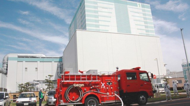 Workers in protective suits transport the water to the reactor building using a fire engine during Emergency Response Training at Fukushima Daini Nuclear Power Station Plant