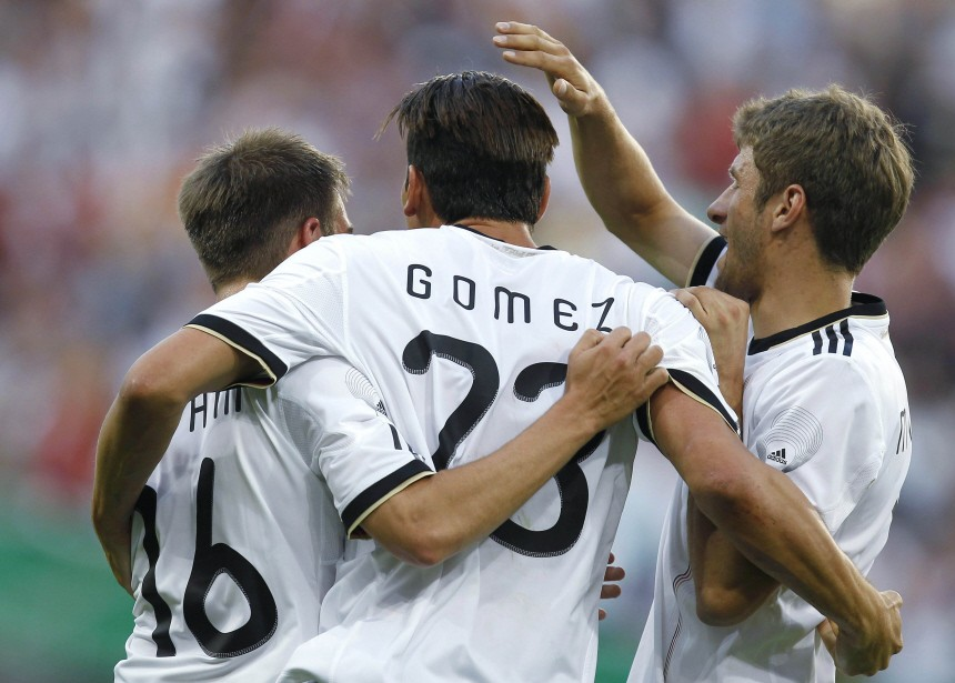 Gomez of Germany celebrates his first goal with his teammates Lahm and Mueller during their international friendly soccer match against Uruguay in Sinsheim