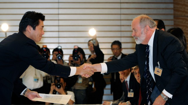 IAEA fact-finding mission team leader Weightman shakes hands with Hosono, special advisor to Japanese Prime Minister Naoto Kan, in Tokyo