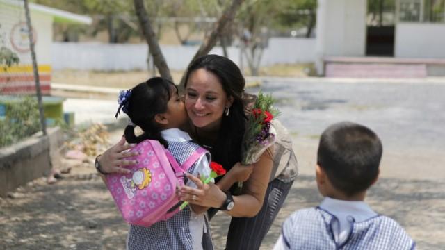 A schoolgirl hugs her teacher Martha Ivette Rivera Alanis before starting clashes at school in a working class neighbourhood in Monterrey