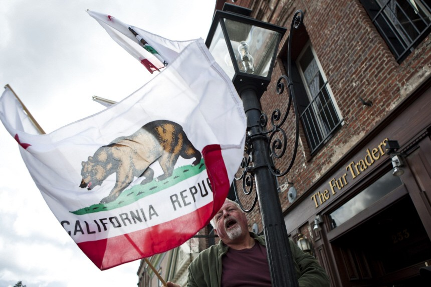 Gary Tintle hangs California's state flag at the start of Stage 2 of the Amgen Tour of California in Nevada City