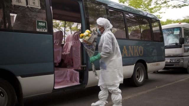 Atomkatastrophe in Fukushima: Reise in die Heimat: Im Schutzanzug besteigt ein Japaner einen Bus, der ihn in die Evakuierungszone bei Fukushima-1 bringen soll. Zweimal mehr Radioaktivität als bisher gemeldet ist dort ausgetreten, räumte die Regierung in Tokio nun ein.