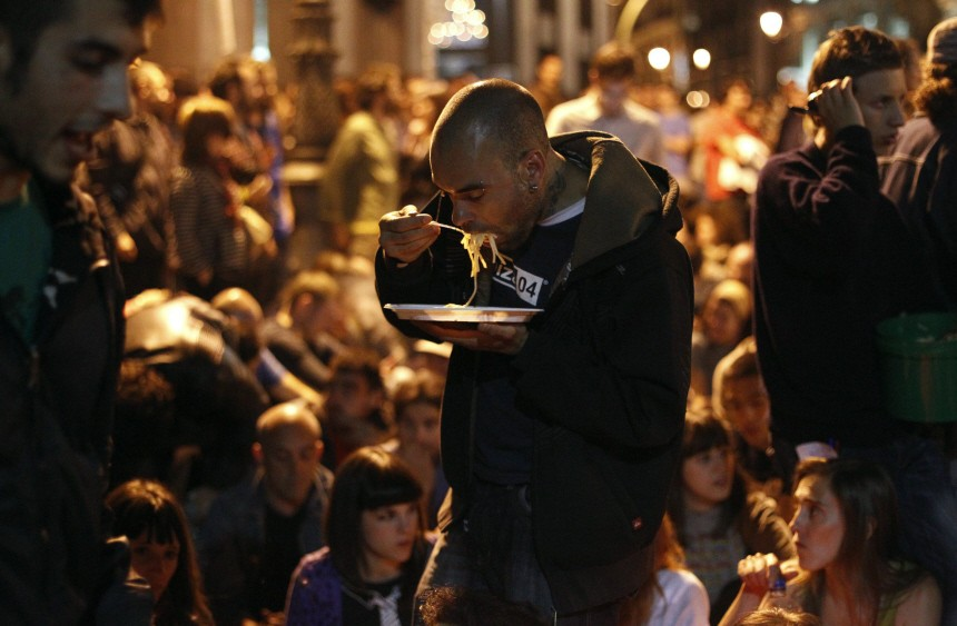 A demonstrator eats pasta as other fellow demonstrators who have been staging a protest in Madrid's Puerta del Sol since March 15, do a sit-in in front of Spain's parliament