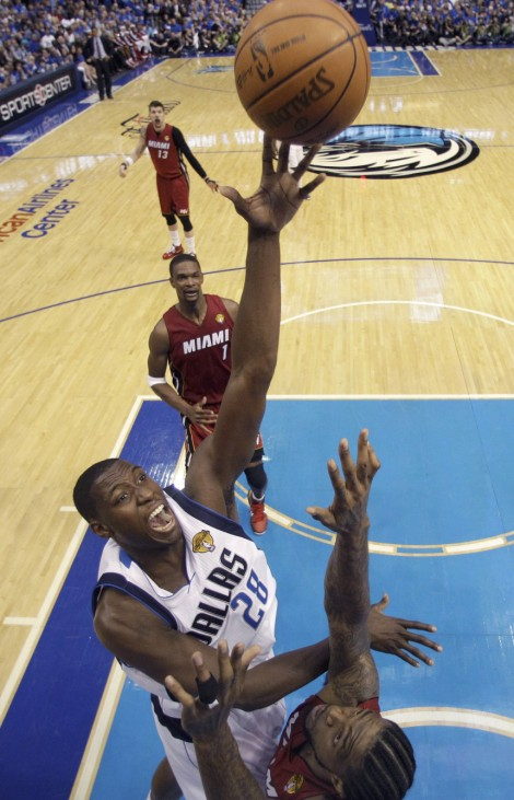 Dallas Mavericks Mahinmi goes over Miami Heat's Haslem for a basket during Game 3 of the NBA Finals basketball series in Dallas