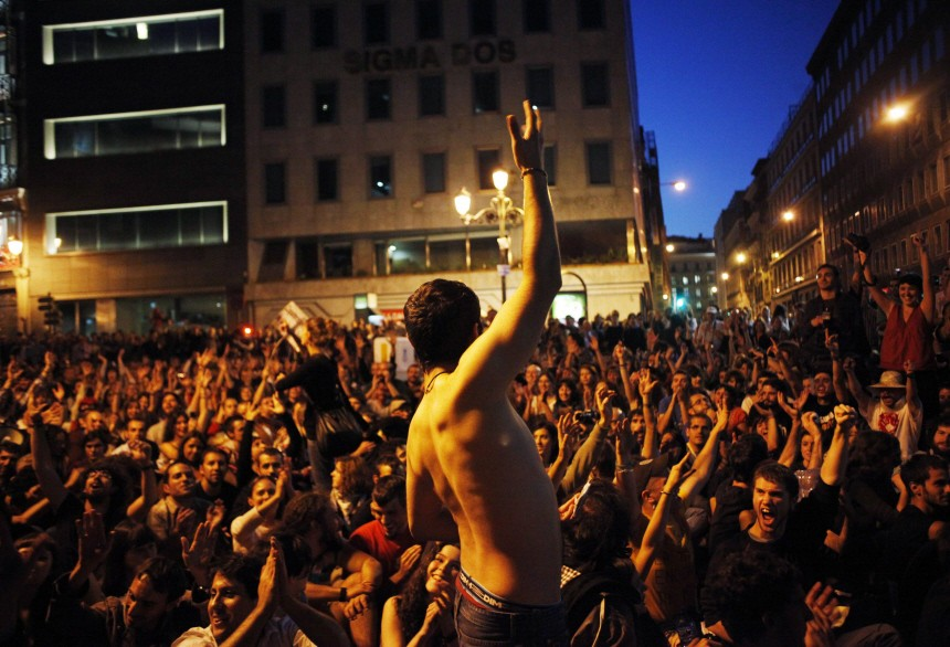 Demonstrators who have been staging a protest in Madrid's Puerta del Sol since March 15 raise their arms in front of Spain's parliament