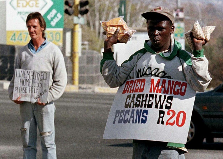 BLACK STREET VENDOR SELLS GOODS AS WHITE MAN BEGS FOR MONEY AT INTERSECTION