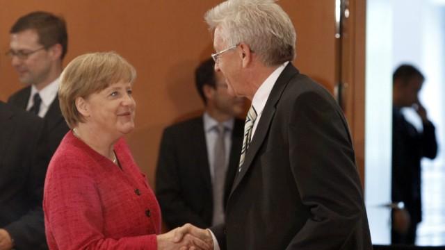 German Chancellor Angela Merkel shakes hands with Baden-Wuerttemberg  State Premier Kretschmann before meeting in Berlin