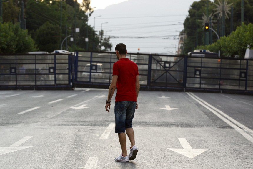 A protester walks in front of a police barrier outside the Greek parliament in Athens