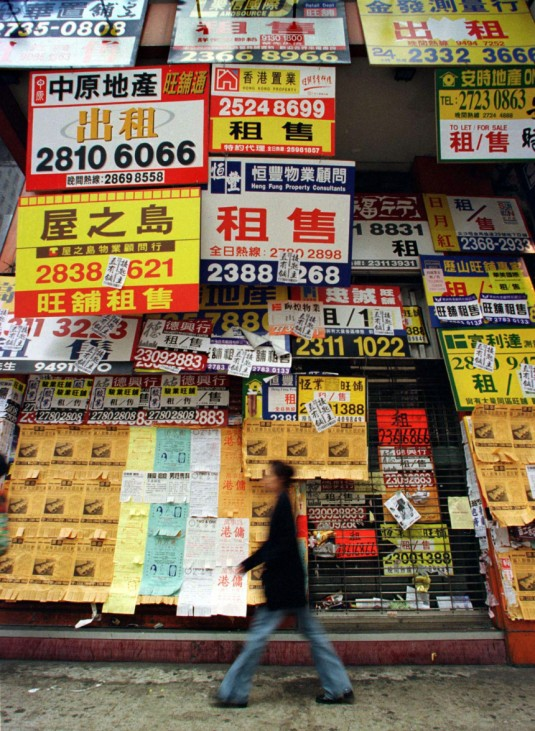 A RESIDENT WALKS PAST A CLOSED PROPERTY SHOP IN HONG KONG